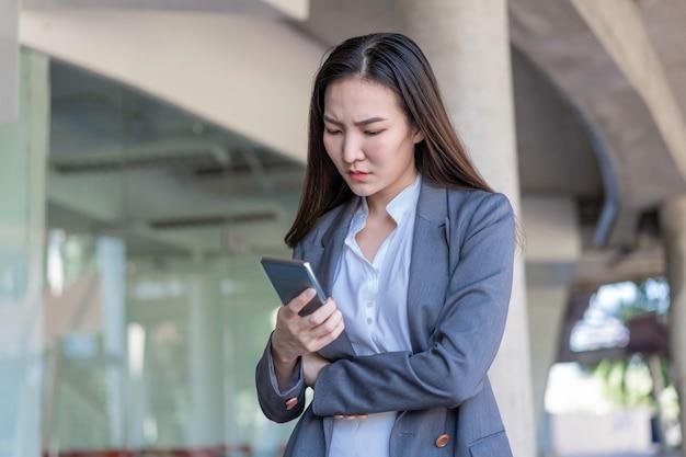 働く女性のコンセプト若い実業家は、たくさんの仕事をし、電子機器に多くの時間を費やした後に疲れました。
