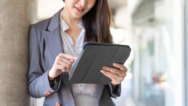 働く女性のコンセプトは、職場の外で、ハンドルデバイス、タブレットを使用してオンラインでビジネスに取り組んでいる若い実業家です。