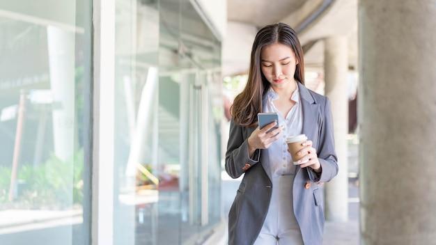 일하는 여성 개념은 화상 회의에 참석하고 커피 한 잔을 들고 있는 젊은 여성 관리자입니다.