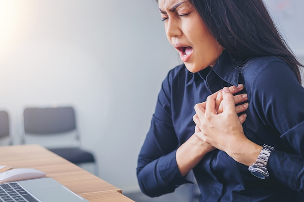 Working woman face suffering and holding breast because of heart infarction in office