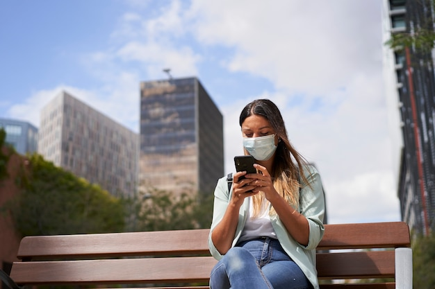 Работающая женщина в городе, сидя на скамейке, с помощью смартфона. он носит маску от пандемии коронавируса.
