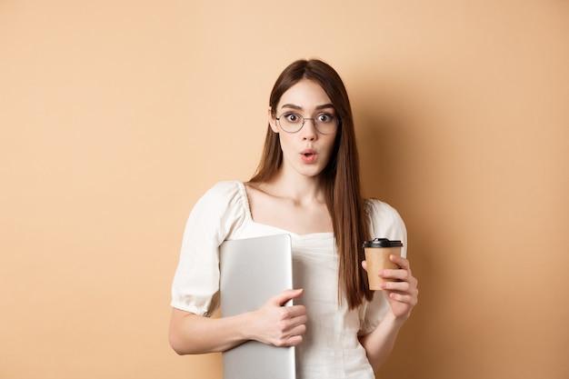 Работающая женщина в очках, держащая ноутбук и кофе, выглядит взволнованной, слышит удивительные новости, стоя на бежевом фоне.