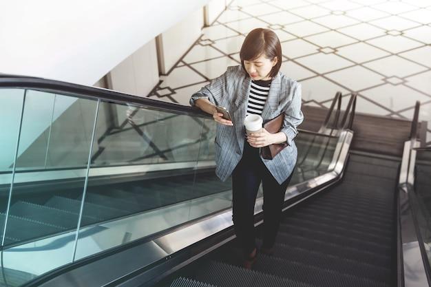 Working woman use smart phone while escalator