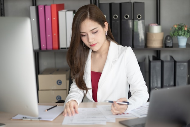 A working woman in white suit is working in office. she is a good looking and smart manage