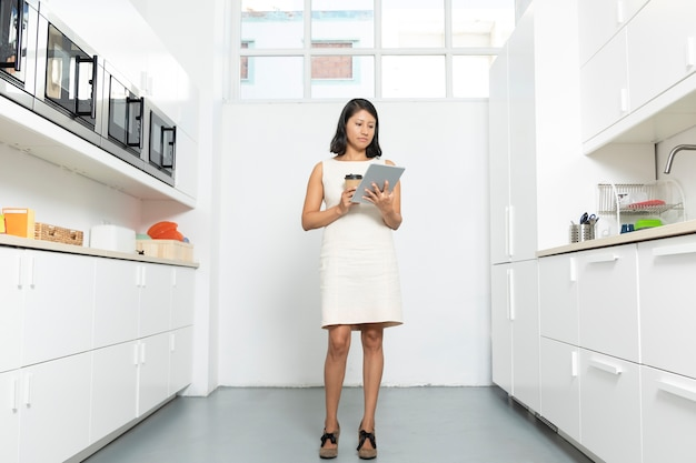 Working woman with tablet in kitchen