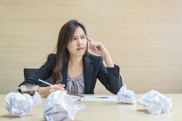 Работающая женщина, работающая с думающим лицом и карандашом на руке