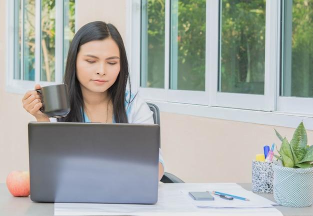 働く女性とコーヒーカップと机の上のループトップコンピュータ