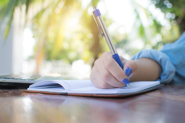 働く女性は、オフィスの外でノートに書くためにペンを持っています。