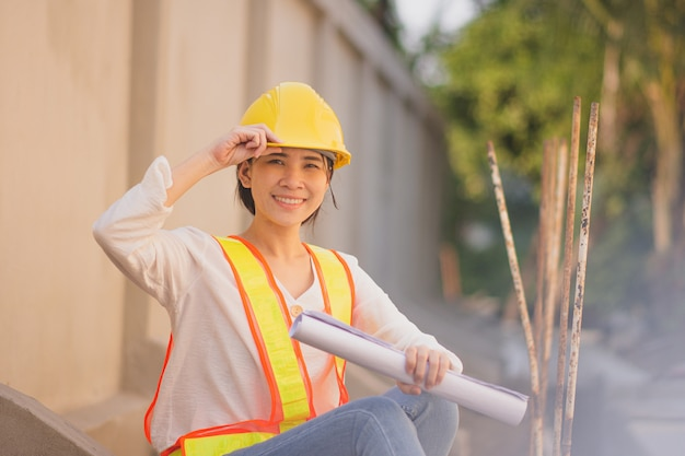 Working women holding blueprint paperwork document  standing at building construction,she is foreman control project