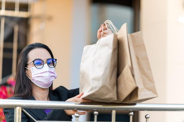持ち帰り用の紙袋を持って働く女性、宅配、テイクアウト