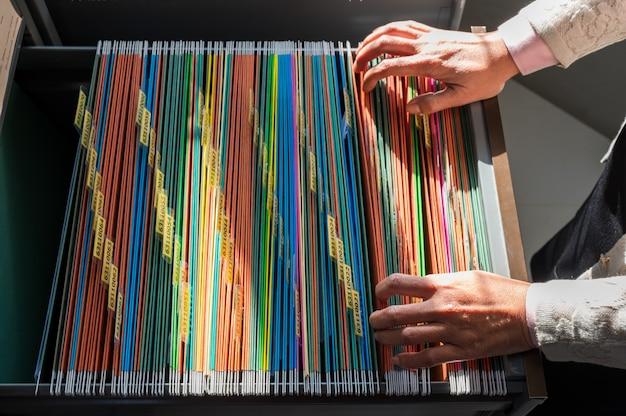 Работающие женщины ищут красочные папки, разложенные по картотечным шкафам.