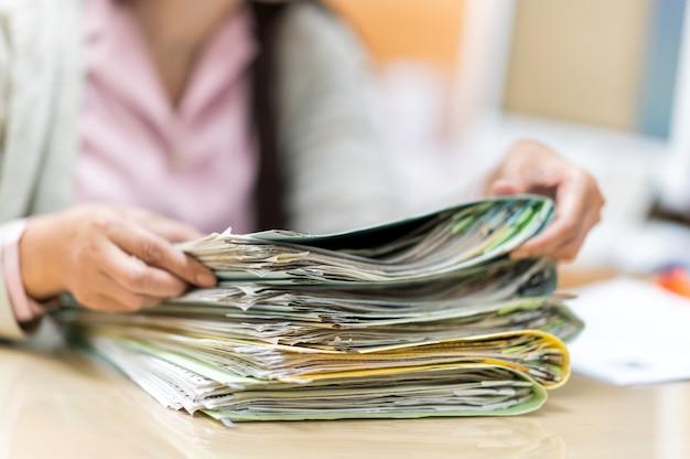机の上でファイルを探している働く女性 Premium写真