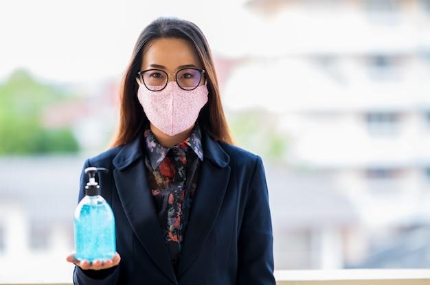 働く女性はサニタリーマスクを着用し、ウイルスを防ぐためにアルコールジェルで手を洗う