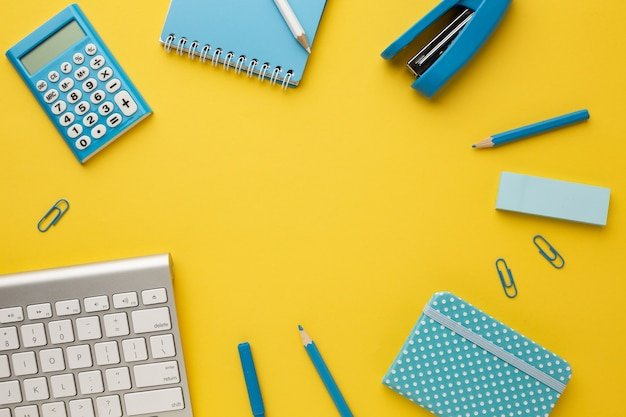 Working yellow table with a keyboard, calculator, notebooks, eraser, pencil, felt-tip pen, stapler and paper clips. flat lay