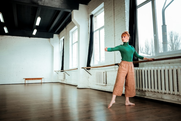 Working. young professional modern dancer with red hair looking focused while training near ballet bar