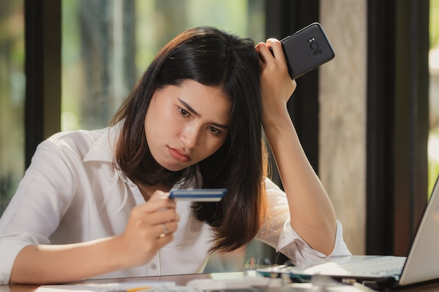 Workingwoman  using smartphone and looking at a card with wonder.
