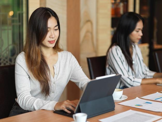 동료와 책상 위에 있는 문서와 함께 사무실에서 노트북 작업을 하는 여성