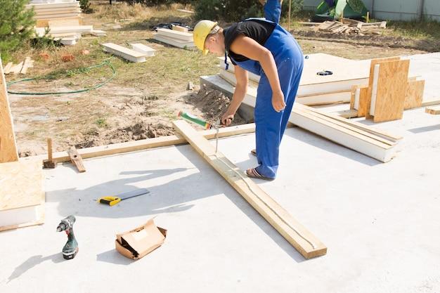 Рабочий наносит столярный клей на изолированную деревянную балку, которую нужно разместить в углу стены на строительной площадке нового дома