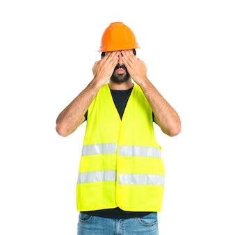 Operaio che copre gli occhi su sfondo bianco isolato