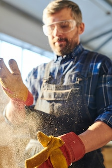 Workman dusting off hands
