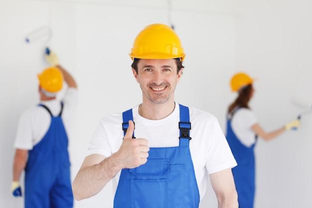 노동자 두 화가 앞에서 엄지 손가락을 포기