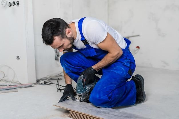 Рабочий в синей спецодежде распиливает ламинатные доски с электрической пилой
