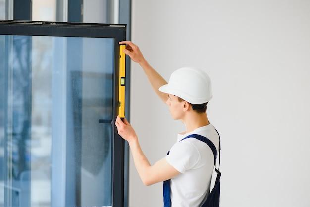 집에서 거실에 플라스틱 창문을 설치하거나 조정하는 작업복의 노동자