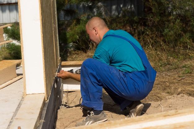 패널의 바닥을 정렬하기 위해 바닥에 무릎을 꿇고 건축 현장에 단열 벽을 설치하는 작업자