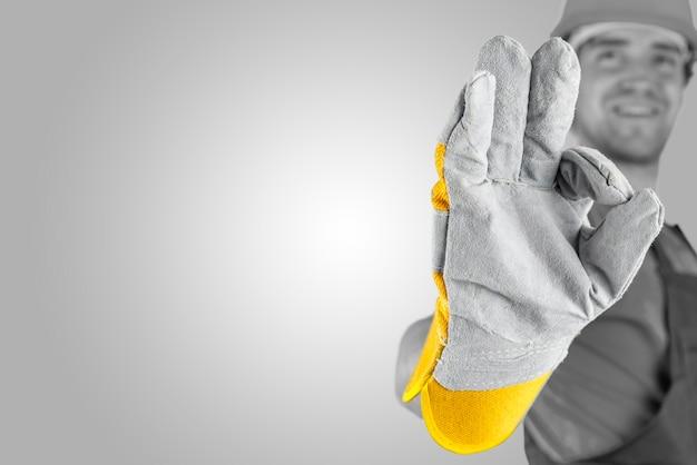 하이라이트와 카피스페이스가 있는 회색 배경 위에 손에 초점을 맞춘 장갑을 낀 손으로 완벽한 몸짓을 하는 노동자.