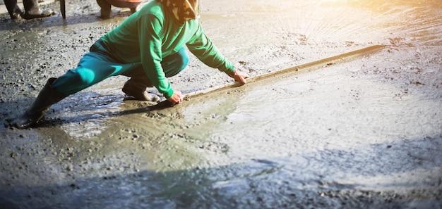 Workman plaster at construction site,concrete pouring during commercial concreting floors.
