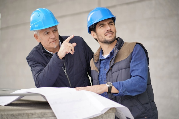 Workman pointing and showing something to employee on modern building sight