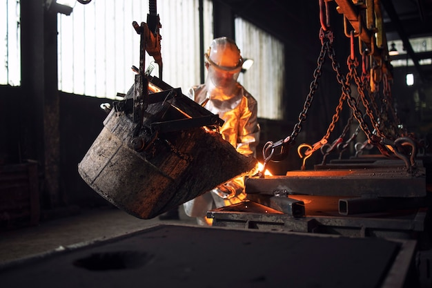 Workman in protective suit hardworking with liquid metal in foundry.
