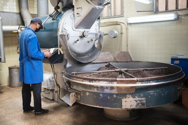 구이 기계에 서 있는 노동자. 로스팅 장비에서 작업하는 커피 로스터의 전망.