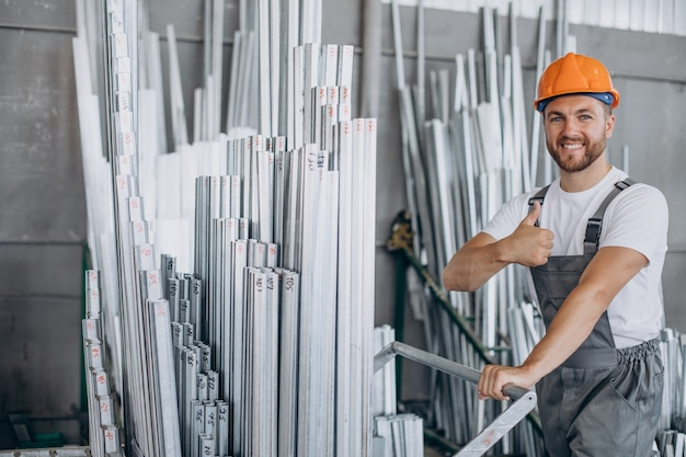Workman at store house in orange helmet