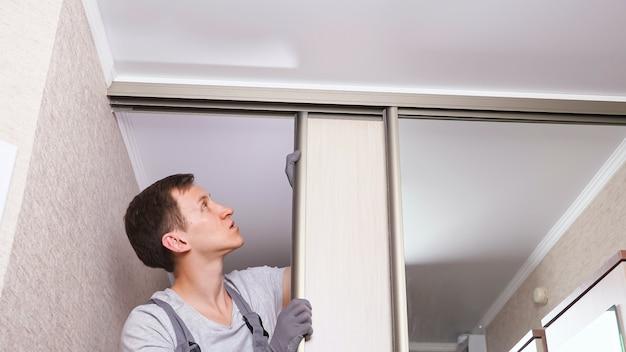 Workman in uniform fixes wooden sliding door of wardrobe