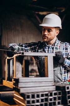 Рабочий в шляпе с измерительной линейкой на заводе