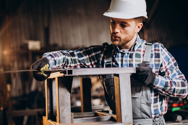 Workman wearing har hat with measuring ruler at factory
