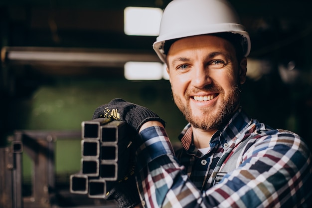 Workman wearing hard hat working with metal constructions at factory