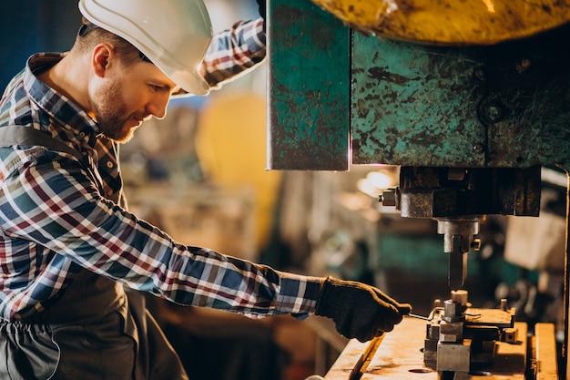 Рабочий в каске работает с металлической трубкой на заводе