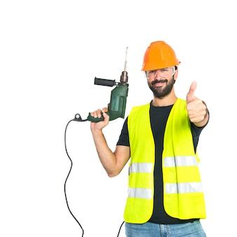 Lavoratore con trapano su sfondo bianco