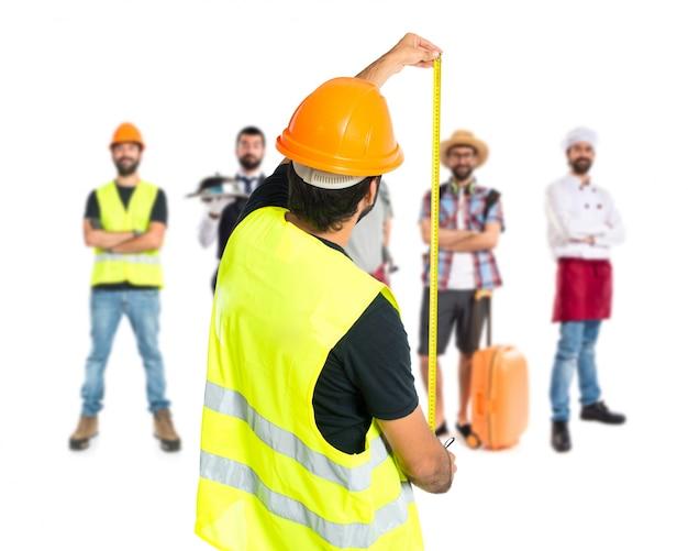 Работник с метром на белом фоне