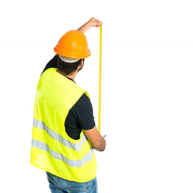白い背景の上にメートルを持つ労働者