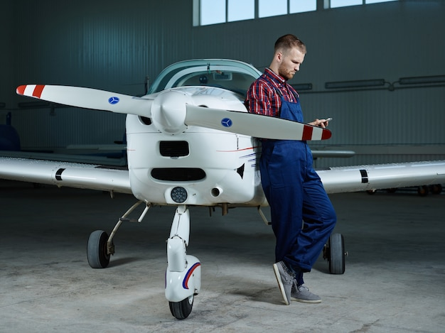 Workman with smartphone and a plane