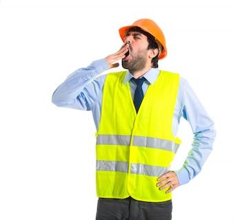 Workman yawning over white background