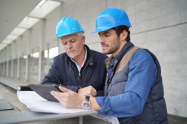 Workmen consulting over blueprint with tablet on modern building sight