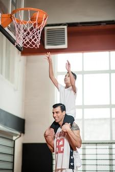 연습. 공을 링에 던지는 동안 소년을 sholders에 안고 코치