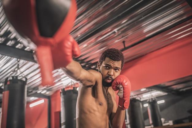 Тренировка. афро-американский кикбоксер тренируется в тренажерном зале и выглядит сосредоточенным