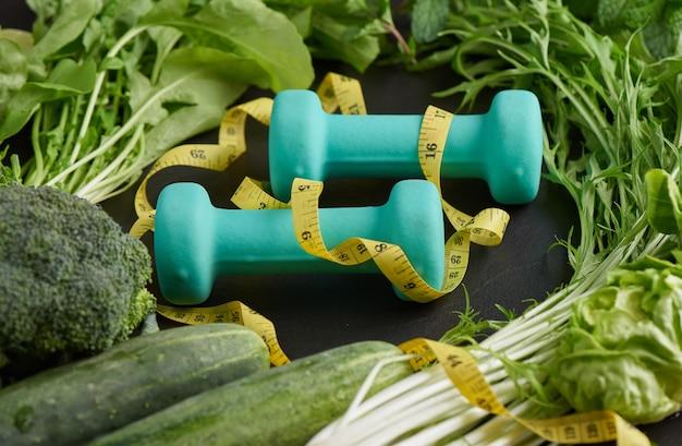 トレーニングとフィットネスダイエット。果物、野菜、ダンベルを使った健康食品のきれいな食事の選択。健康食品のコンセプトの選択。