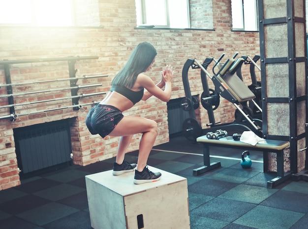 운동 개념. 스포츠에서 갈색 머리 여자는 체육관에서 나무 상자에 crouches. 다시보기. 기능 훈련