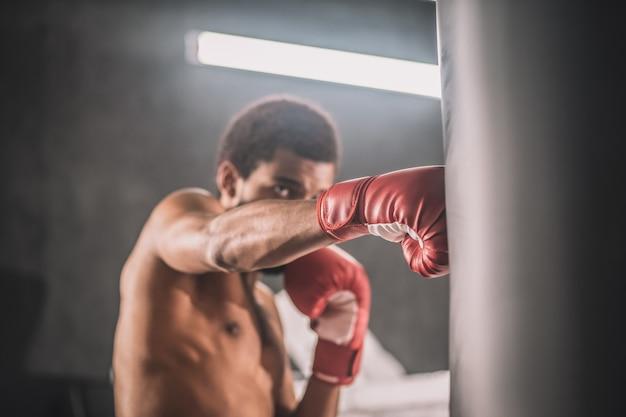 Тренировка. темнокожий кикбоксер тренируется в тренажерном зале и выглядит вовлеченным